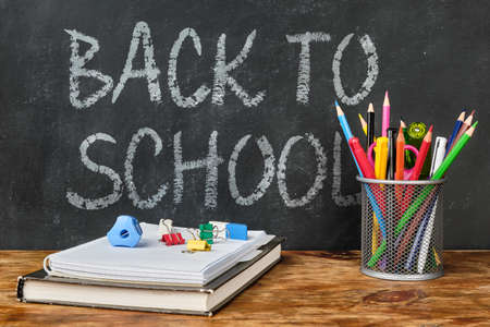 Back to school lettering with school supplies such as textbook, notebook, pens, pencils, scissors and other over chalkboard background