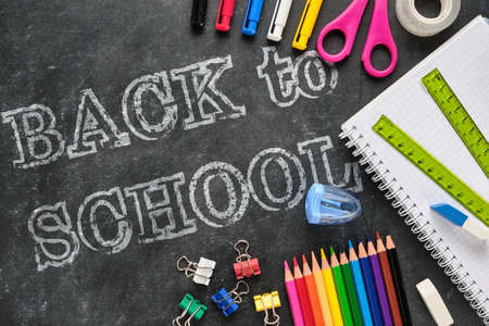 Back to school lettering with school supplies such as ruler, notebook, pens, pencils, scissors and other on chalkboard Stockfoto