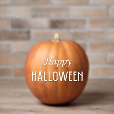 Halloween background with defocused pumpkin against a brick wall and Happy Halloween lettering