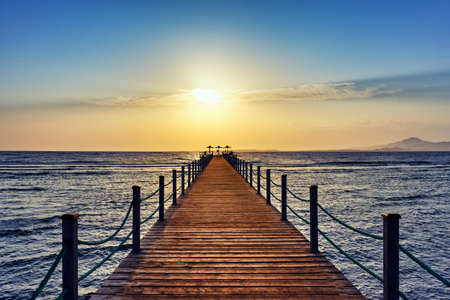 Bright and colorful sunrise over the sea and pier. Perspective view of a wooden pier on the sea at sunrise with rocky islands in the distance