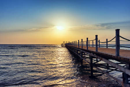 Bright and colorful sunrise over the pier and sea. Perspective view of a wooden pier on the sea at sunrise with rocky islands in the distance Stockfoto