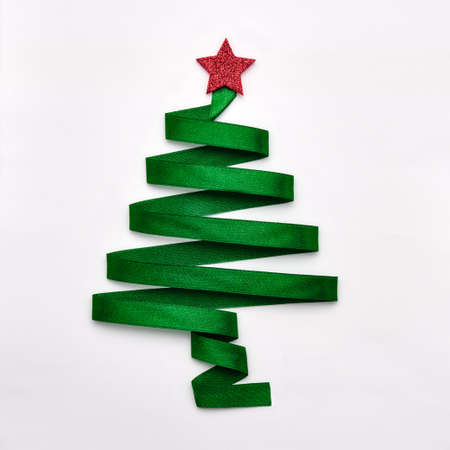 Stylized Christmas tree made from green ribbon with red shiny star on white background