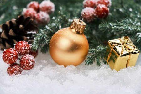 Christmas composition with golden Christmas ball, gift box, red berries and fir branch in the snow Stockfoto