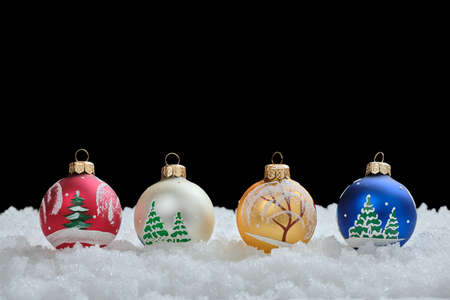 Abstract Christmas composition with Christmas balls on snow flakes, on a black background at the back