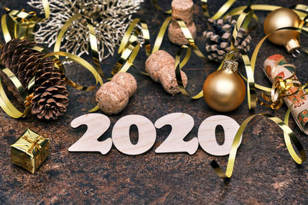New Year 2020 festive background with wooden numbers 2020, pine cones, golden Christmas ball, gift box, and other Christmas decorations