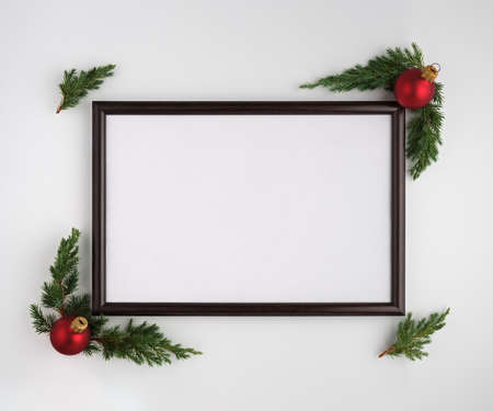 Christmas or New Year composition. Photo frame with copy space, Christmas tree branches and Christmas balls on white background. Flat lay, top view Stockfoto