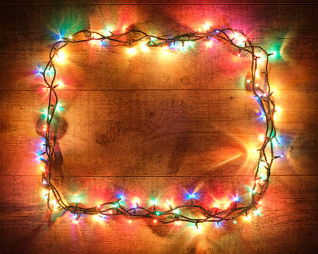 Christmas lights frame. New Year festive decorations with frame of colorful glowing Christmas lights. Colorful garland on a wooden table. Flat lay, top view