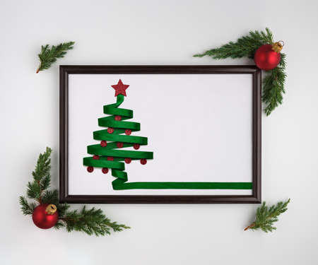 Stylized Christmas tree made from green ribbon with red shiny star and Christmas balls in photo frame on a white background. Flat lay, top view, horizontal layout Stockfoto