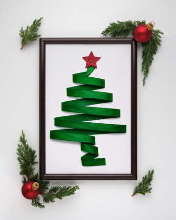 Stylized Christmas tree made from green ribbon with red shiny star and Christmas balls in photo frame on a white background. Flat lay, top view, vertical layout