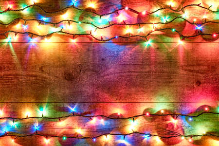 Christmas lights on a wooden background. Bright and colorful New Year festive decorations with glowing Christmas lights. Colorful garland on a wooden table. Flat lay, top view, horizontal layout