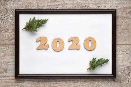 2020 New Years festive composition with wooden numbers 2020 and Christmas tree branches inside a photo frame with a white background. Flat lay, top view, horizontal layout