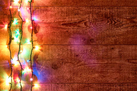 Christmas lights or Colorful garland on the left on a wooden background. Bright and colorful New Year festive decorations with glowing Christmas lights. Flat lay, top view, horizontal layout Stockfoto