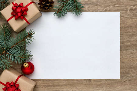 Christmas or New Year composition. White sheet of paper with copy space, gift boxes, Christmas ball and Christmas tree branches on a wooden background. Flat lay, top view, horizontal layout