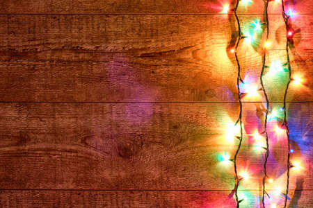 Christmas lights or Colorful garland on the right on a wooden background. Bright and colorful New Year festive decorations with glowing Christmas lights. Flat lay, top view, horizontal layout Stockfoto