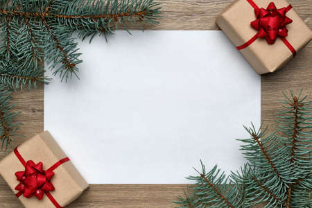 Christmas or New Year composition. White sheet of paper with copy space, gift boxes and Christmas tree branches on a wooden background. Flat lay, top view, horizontal layout Stockfoto