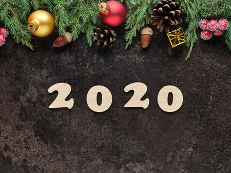 Happy New Year festive background with wooden numbers 2020 and Christmas decorations on a dark stone surface. Top view, flat lay
