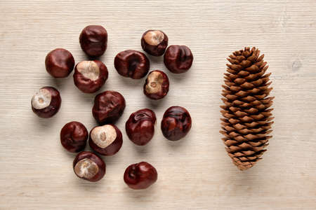 Chestnuts and fir cone on a wooden background. Flat lay, top view