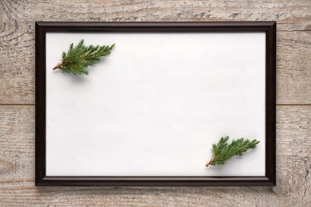 Photo frame with a sheet of white paper with copy space and Christmas tree branches inside on a wooden surface. Flat lay, view from above, horizontal layout