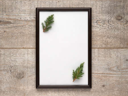 Photo frame with a sheet of white paper with copy space and Christmas tree branches inside on a wooden surface. Flat lay, view from above, vertical layout