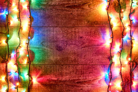 Christmas lights or colorful garland on the sides on a wooden background. Bright and colorful New Year festive decorations with glowing Christmas lights. Flat lay, top view, horizontal layout
