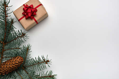 Christmas or New Years composition with a gift box, Christmas tree branches and fir cone on a white background. Copy space, flat lay, view from above