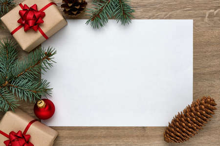 Christmas or New Year background. White sheet of paper with copy space, gift boxes, Christmas balls and Christmas tree branches on a wood. Flat lay, top view