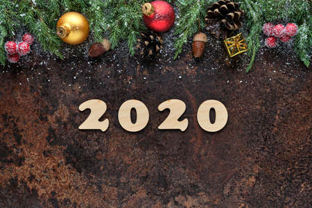 Happy New Year festive background with wooden numbers 2020 and Christmas decorations on a stone surface. Flat lay, view from above