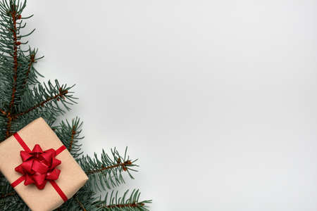 Christmas or New Years composition with a gift box and Christmas tree branches on a white background. Copy space, flat lay, view from above Stockfoto