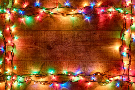 Frame of Christmas lights or colorful garland on a wooden background. Bright and colorful New Year festive decorations with glowing Christmas lights. Flat lay, view from above
