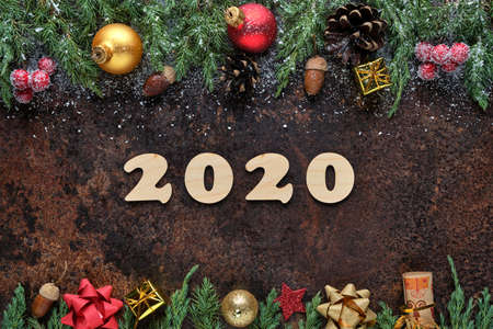 New Years Eve festive background with wooden numbers 2020 and Christmas decorations on a stone surface. Flat lay, view from above