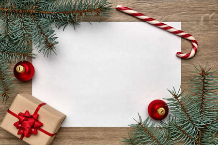 Christmas or New Year composition. White sheet of paper with copy space, gift box, candy cane, Christmas ball and Christmas tree branches on a wooden background. Flat lay, view from above Stockfoto