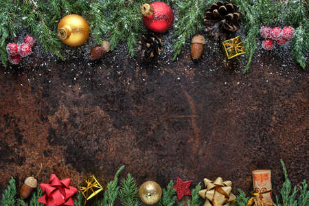 Christmas or New Years flat lay composition. Christmas tree branches, pine cones, Christmas balls, gift box, and other decorations on a stone background. View from above