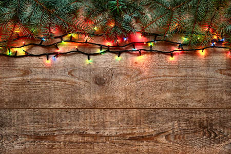 Christmas lights and fir tree branches on a wooden background. New Year festive decorations with colorful glowing Christmas lights. Colorful garland on a wooden table. Flat lay, view from above Stockfoto
