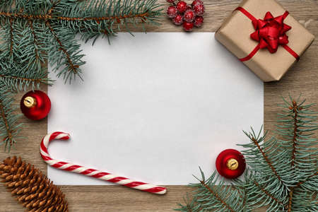 Christmas or New Year composition. White sheet of paper with copy space, gift box, candy cane, Christmas ball and fir tree branches on a wooden background. Flat lay, view from above Reklamní fotografie