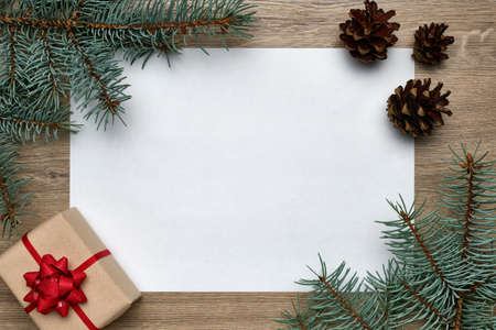 Christmas or New Year background. White sheet of paper with copy space, gift box and Christmas tree branches on a wood. Flat lay, view from above