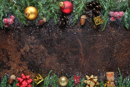 Christmas or New Year flat lay composition. Christmas tree branches, pine cones, Christmas balls, gift box, and other decorations on a stone background. View from above