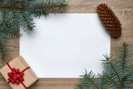 White sheet of paper with copy space, gift box and Christmas tree branches on a wood.