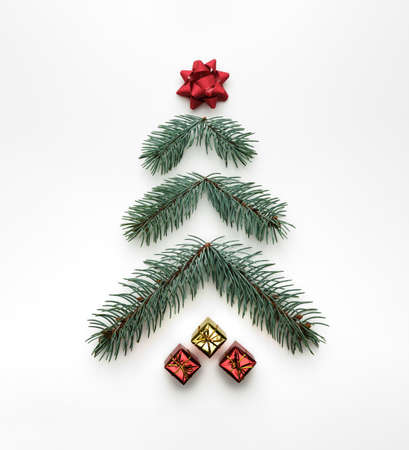 Stylized Christmas tree made of fir branches with gift boxes on a white background. Flat lay, view from above