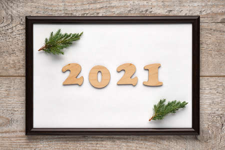 2021 New Years festive composition with wooden numbers 2021 and Christmas tree branches inside a photo frame with white background. Flat lay, top view, horizontal layout 版權商用圖片