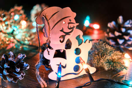 Christmas or New Year background with wooden decorative snowman, pine cone, Christmas lights and fir tree branch. Christmas festive composition with season decorations