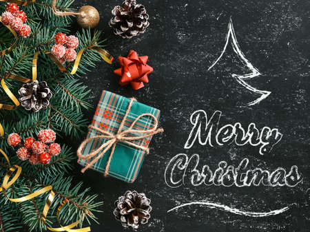 Christmas background with a stylized Christmas tree and Merry Christmas lettering on a chalkboard. New Year composition with a gift box and other holiday decorations 版權商用圖片