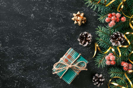 Christmas festive background with a gift box, Christmas tree branches and seasonal decorations on black board. Flat lay. Space for text