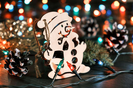 Decorative wooden snowman against the backdrop of blurred christmas lights and other seasonal decorations. Christmas and New Year festive background 版權商用圖片