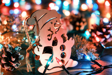 Decorative wooden snowman against the backdrop of blurred christmas lights and other seasonal decorations. Christmas and New Year holiday background 版權商用圖片 - 158294256