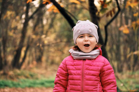 Adorable and happy little girl 2-3 years old outdoors in autumn forest or park. Emotions of joy and surprise
