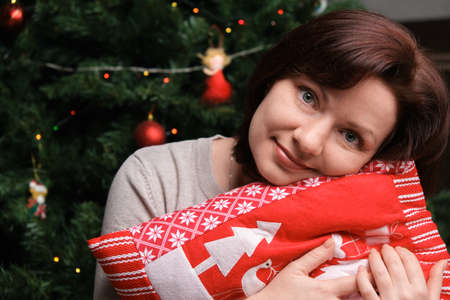 Happy young beautiful smiling woman posing near Christmas tree hugs red pillow with Christmas tree and Santa Claus. Close-up portrait. Looks into the camera 版權商用圖片 - 158903786