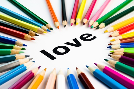 Detail view of many colored pencils arranged in circle on the word love Stockfoto