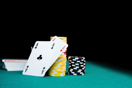 Gambling chips, a stack of cards & two aces