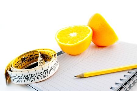 nutrici�n: detalle de una naranja con una cinta m�trica en el bloc de notas Foto de archivo