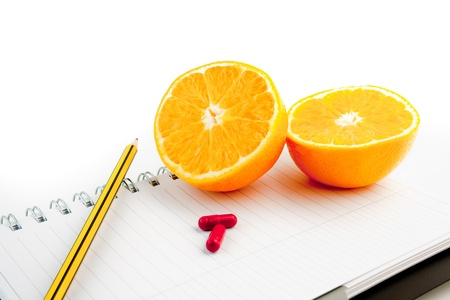 detail an orange with a pencil on notepad photo